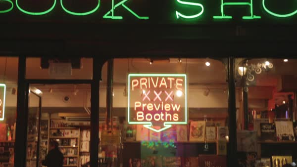 Hand-held shot of a bookstore with a sign advertising adult content Royalty-free stock video
