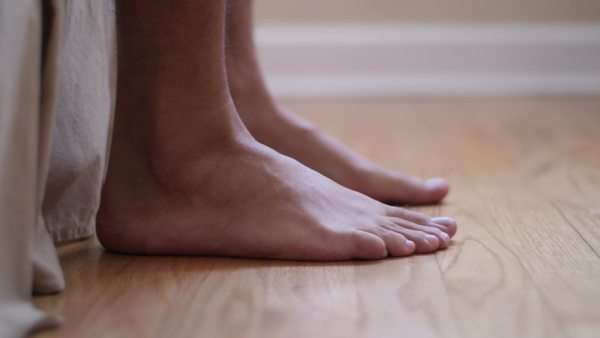 Bare Feet Stepping Out Of Bed Onto Floor In The Morning