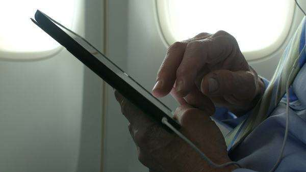 Hands using a tablet on an airplane Royalty-free stock video