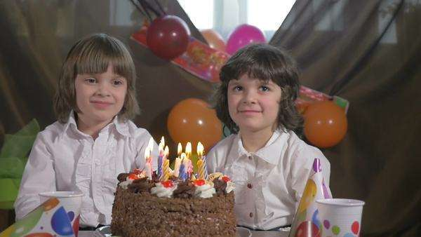 Young Beautiful Twin Sisters Blowing Candles On A Birthday Cake Slow Motion Royalty Free