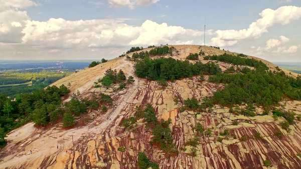 Aerial of Stone mountain with antenna on top, on a bright, cloudy day, hikers walking, running, talking and socializing, enjoying great view, on a bright, cloudy summer afternoon Royalty-free stock video