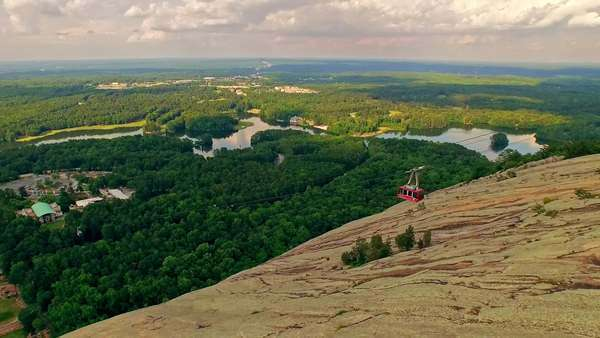 Aerial of gondola lift with passengers, descending Stone mountain on a bright, cloudy summer afternoon with an incredible view of city scape among forests and lakes illuminated by warm sunlight Royalty-free stock video