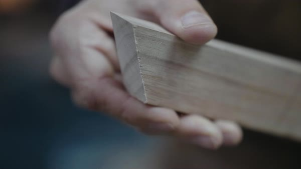 Hand-held shot of a carpenter holding and inspecting a piece of wood Royalty-free stock video
