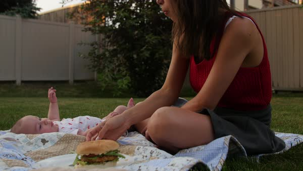 Young mom eats veggie burger on lawn with infant son Royalty-free stock video