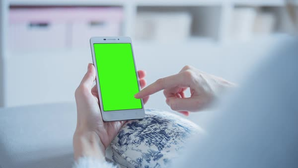 Young woman sitting on a couch uses smartphone with pre-keyed green screen. Few types of motion - scrolling up and down, tapping, zoom in and out. Royalty-free stock video