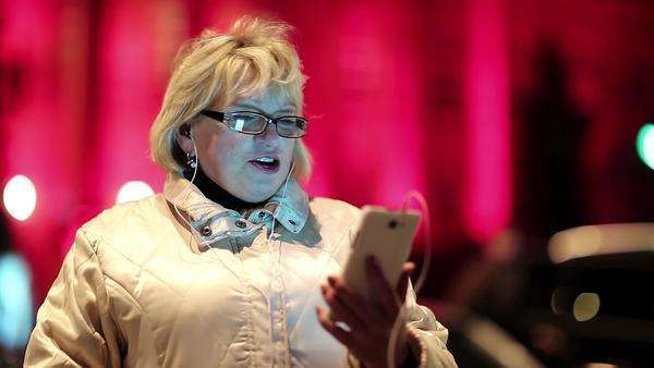 Senior woman standing near the road in nighttime and communicates via smartphone. Cheerful blonde woman with glasses standing near the road and talks in skype on the mobile phone, she say hello Royalty-free stock video