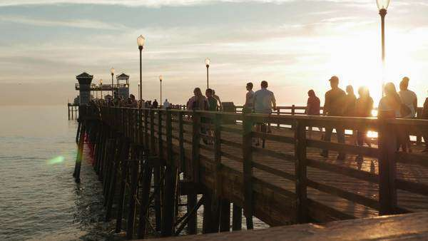 Wide shot of a broad walk with people at sunset Royalty-free stock video