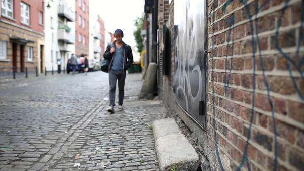 Wide shot of a young man walking on a street in Dublin Royalty-free stock video