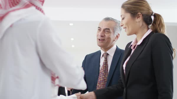 Smiling Western & Arab business people meeting & shaking hands in office. Royalty-free stock video