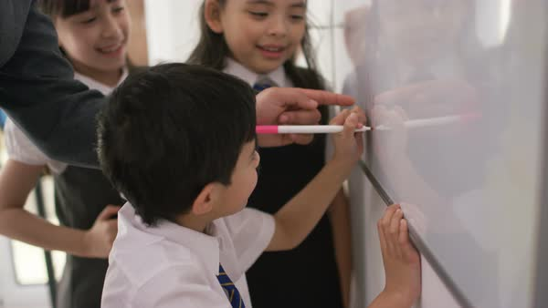 Happy school children in class writing on board with teacher. Royalty-free stock video