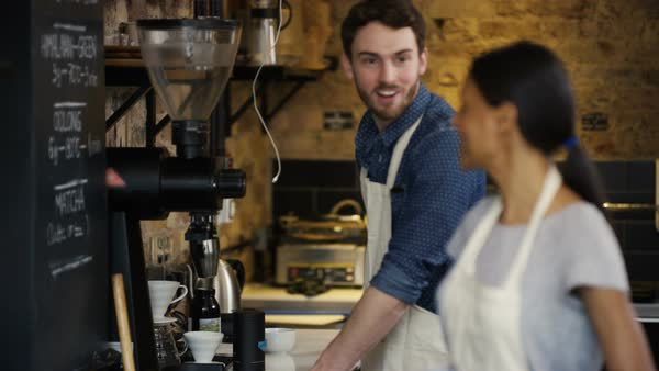 Portrait of friendly smiling worker or business owner standing behind counter in coffee shop. Royalty-free stock video