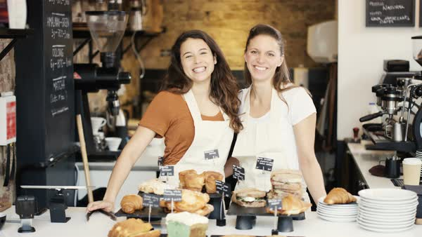 Portrait of friendly smiling worker or business owners standing behind counter in coffee shop. Royalty-free stock video