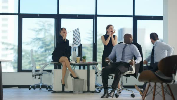 Bored business team have fun racing chairs around the office Royalty-free stock video