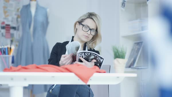 Smiling dressmaker in her studio, looking at magazine for inspiration Royalty-free stock video
