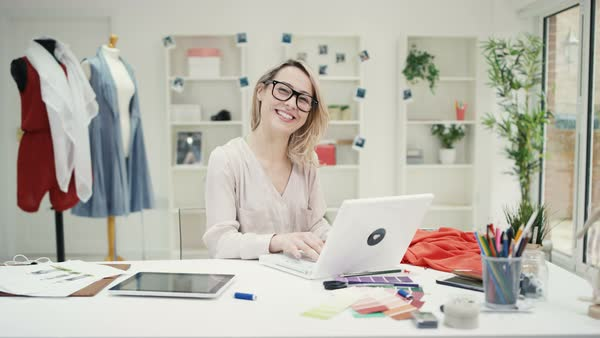 Portrait of smiling fashion designer working at her desk in creative studio Royalty-free stock video