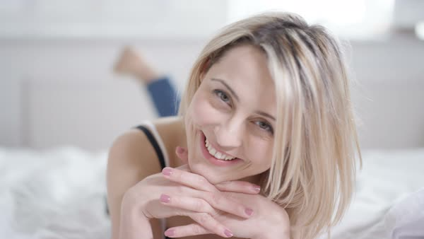 Attractive woman relaxing at home, lying on bed and smiling to camera Royalty-free stock video