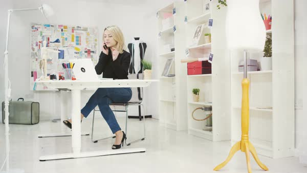 Fashion designer in her studio, working on laptop and talking on phone Royalty-free stock video