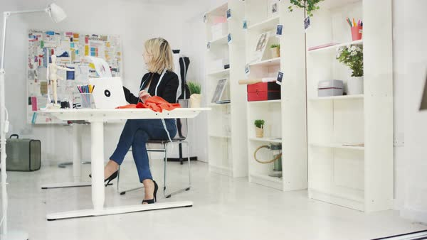 Portrait of smiling fashion designer working on laptop computer at her desk Royalty-free stock video