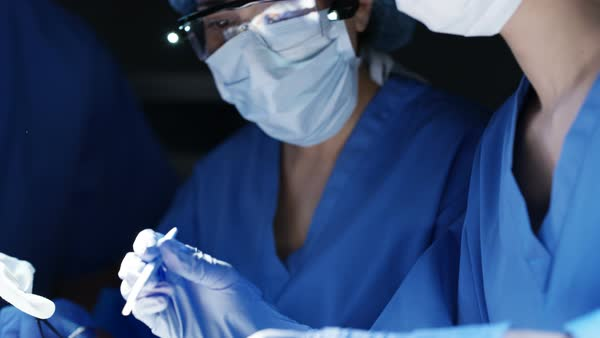 Team of surgeons in operating theater performing operation on a patient. Royalty-free stock video