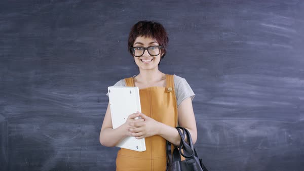 Portrait smiling woman holding laptop on blank chalkboard background Royalty-free stock video