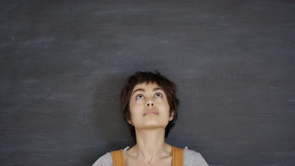 Close up portrait smiling woman looking up on blank chalkboard background Royalty-free stock video