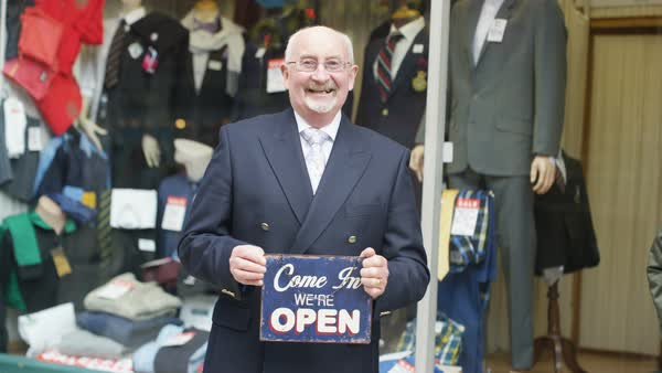 Happy shopkeeper holds up a sign to show he is open for business Royalty-free stock video