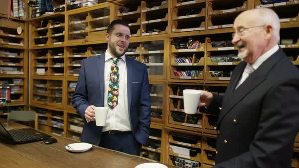 Shopkeepers in man's clothing store standing behind counter with hot drinks Royalty-free stock video