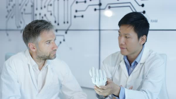 Scientific research engineers collaborating on project to build robotic hand Royalty-free stock video