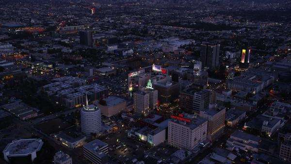 Aerial view of Los Angeles at Night. Helicopter shot flying over city business offices, suburban homes and streets at dusk. Royalty-free stock video