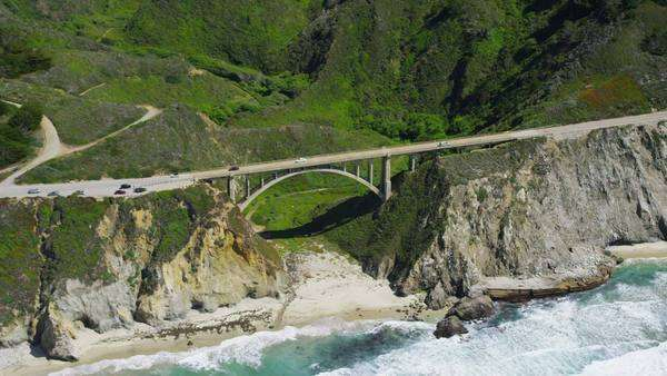 Aerial view of a bridge span. California Coastline along the Big Sur. Road and cliffs overlooking the blue ocean. Royalty-free stock video