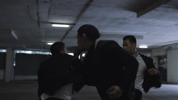 Asian gangster fighting in dark parking lot with members of a rival gang Royalty-free stock video