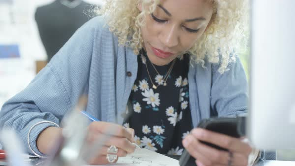 Jewelry designer at her desk sketching out designs and looking at smartphone Royalty-free stock video