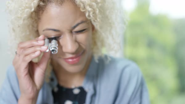 Jewelry maker in her studio looking through a loupe to check quality of ring. Royalty-free stock video