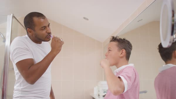 Father   son in bathroom brushing their teeth together Royalty free stock  video. Cute young brother   sister in bathroom  looking in mirror