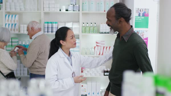 Worker in a pharmacy assisting mature gentleman Royalty-free stock video