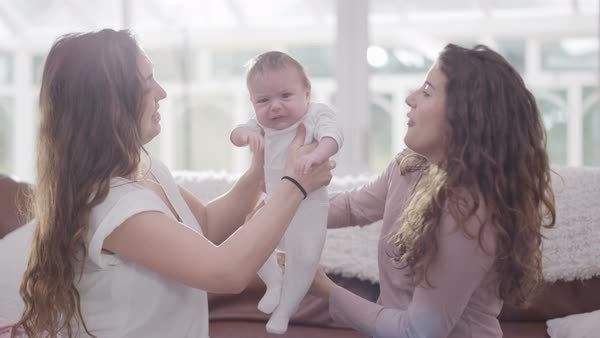 New mother with friend or family member holding crying baby daughter at home. Royalty-free stock video