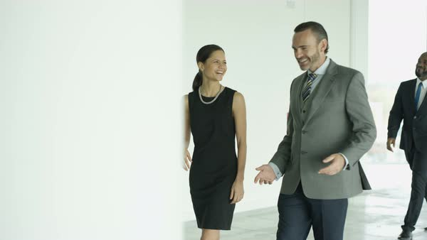 Business man and woman chatting as they walk through busy modern office Royalty-free stock video