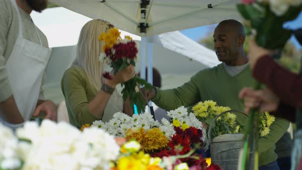 Cheerful customers buying fresh flowers at outdoor summer market. Royalty-free stock video