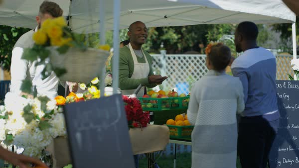Friendly stall holders selling to customers at a farmers market, fresh cut flowers and fruit and vegetables on display. Royalty-free stock video