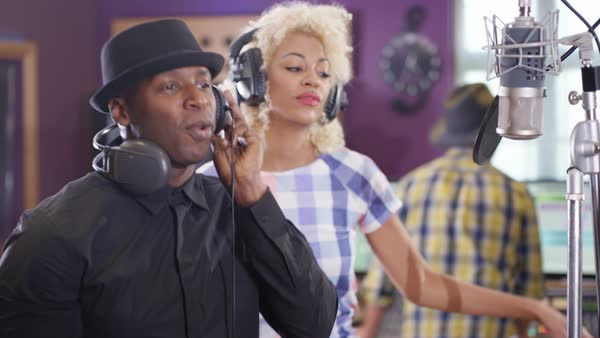 Young black music artists singing into microphone in recording studio, sound engineer working in background. Royalty-free stock video