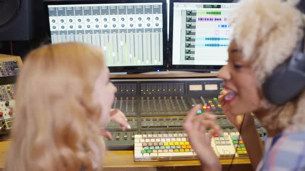 Two young women in recording studio working at the mixing desk. Royalty-free stock video