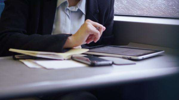 Young female executive working on her digital tablet and smartphone on a commuter train. Royalty-free stock video