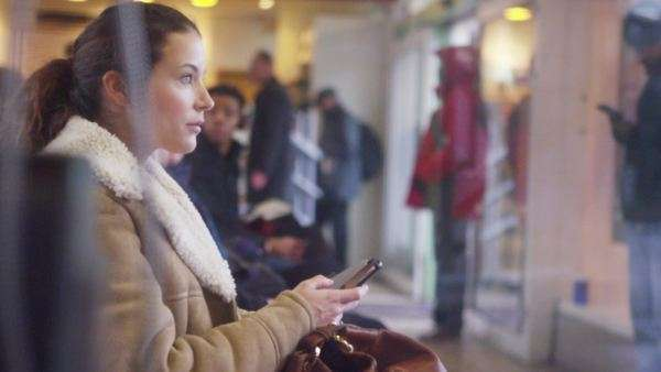 Attractive, young female using digital tablet in subway station or waiting room. Royalty-free stock video