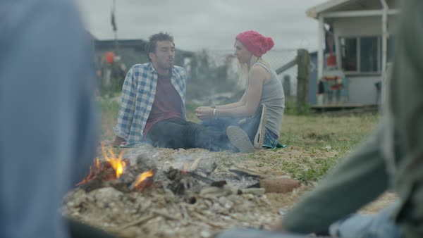 Happy friends sitting around a bonfire on the beach, young couple talking and relaxing together. Royalty-free stock video