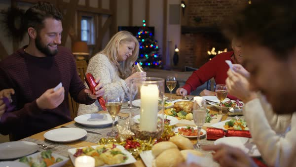 Happy family together at Christmas, pulling crackers at the dinner table. Royalty-free stock video