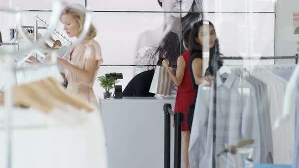 Male sales assistant taking payment from female customer in a boutique clothing store. Royalty-free stock video