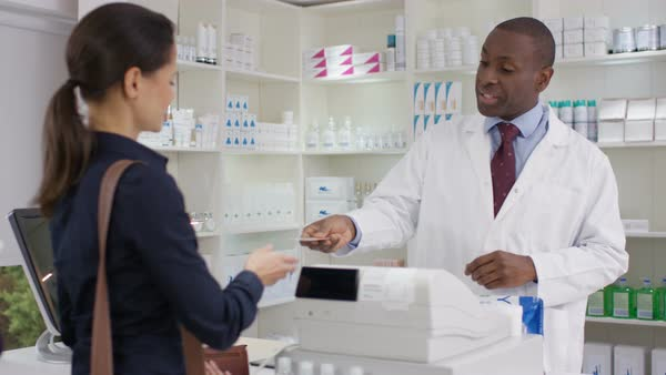 Friendly pharmacy worker serving customers and taking payment at the till. Royalty-free stock video
