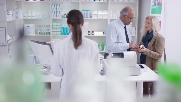 Team of staff working and serving customers in a chemist shop. Royalty-free stock video