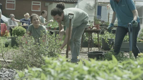 Cheerful volunteers of mixed ages working together in community garden. Royalty-free stock video
