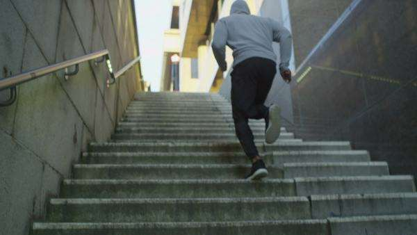Athletic man running up steps through urban environment Royalty-free stock video